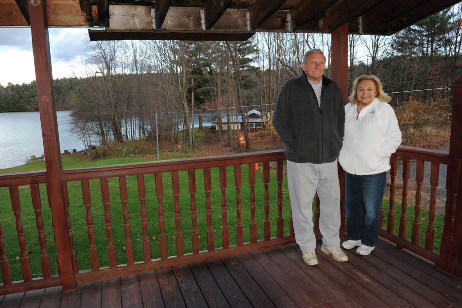Walter and Rosemary Spallane stand on their porch on Friday Nov. 2, 2012 in Nassau, N.Y. The portion of their property seen in the background by the lake is facing an adverse possession claim. (Lori Van Buren / Times Union) Photo: Lori Van Buren