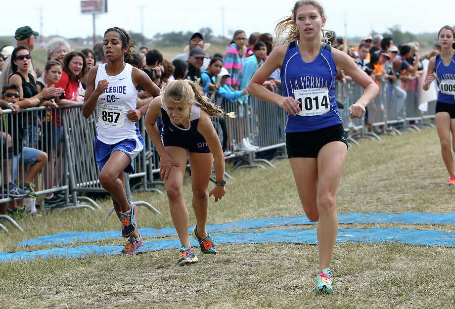 La Vernia's Bailee Vrana (right) finishes in second place, Ingleside's Naira Alvarado (left) finishes in third place and Boerne's Ashlynn Tucker (center) finishes in fifth after she fell at the homestretch of the finish line in the Division 3A girls race at the Region IV Cross Country Meet on Saturday, Nov. 3, 2012. Photo: Kin Man Hui, Express-News / © 2012 San Antonio Express-News