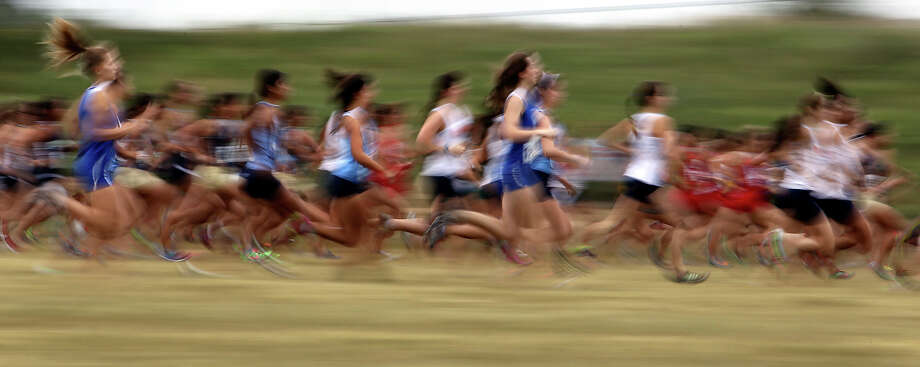 Division 5A girls blur past on the start of their race at the Region IV Cross Country Meet on Saturday, Nov. 3, 2012. Photo: Kin Man Hui, Express-News / © 2012 San Antonio Express-News