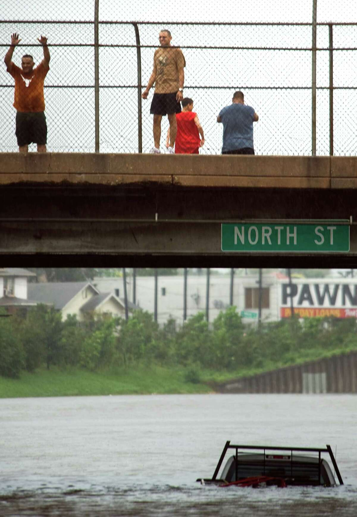 Onlookers pause on a bridge to survey floodwater covering Interstate 45 just north of downtown Houston after the passage of Hurricane Ike, Saturday, Sept. 13, 2008. ( Smiley N. Pool / Chronicle )