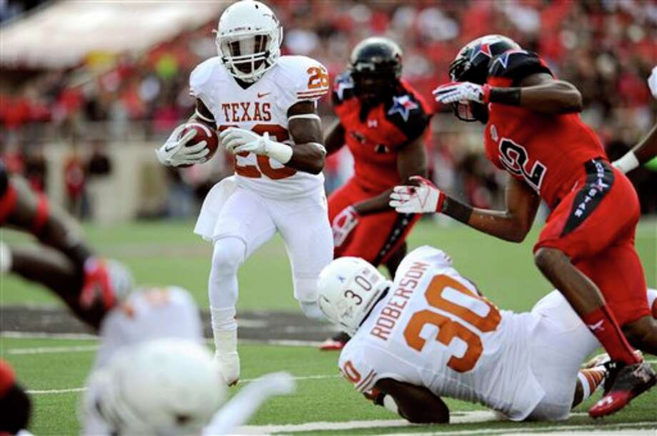 Texas running back D.J. Monroe runs through the Texas Tech defense during the first half of their NCAA college football game, Saturday, Nov. 3, 2012, in Lubbock, Texas. Texas won 31-22. (AP Photo/The Daily Texan, Elisabeth Dillon) Photo: Elisabeth Dillon, AP / The Daily Texan