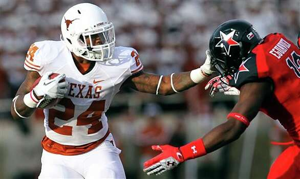Texas' Joe Bergeron shoves away Texas Tech's Sam Eguavoen during their NCAA college football game, Saturday, Nov. 3, 2012, in Lubbock, Texas. Texas won 31-22. (AP Photo/Lubbock Avalanche-Journal, Stephen Spillman)  LOCAL TV OUT Photo: Stephen Spillman, AP / The Avalanche-Journal