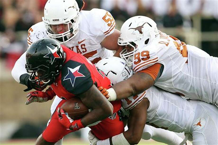 Texas Tech's Kenny Williams is tackled by Texas' Dalton Santos (55), Tevin Jackson (11) and Desmond Jackson during their NCAA college football game, Saturday, Nov. 3, 2012, in Lubbock, Texas. Texas won 31-22. (AP Photo/Lubbock Avalanche-Journal, Stephen Spillman)  LOCAL TV OUT Photo: Stephen Spillman, AP / The Avalanche-Journal