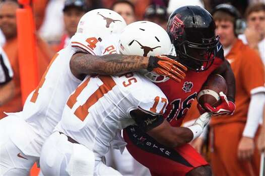 Texas linebacker Tevin Jackson (11) and safety Kenny Vaccaro (4) tackle Texas Tech wide receiver Micah Awe (18) during their NCAA college football game, Saturday, Nov. 3, 2012, in Lubbock, Texas. Texas won 31-22. (AP Photo/The Odessa American, Albert Cesare) Photo: Albert Cesare, AP / The Odessa American