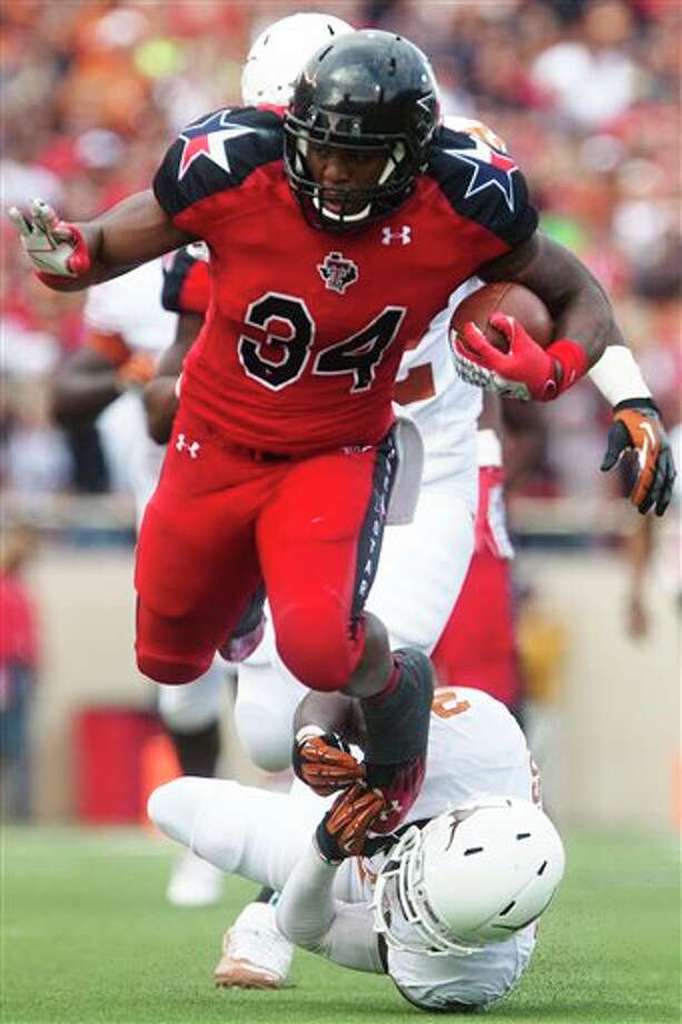 Texas Tech running back Kenny Williams (34) is tripped up by Texas safety Mykkele Thompson (2) during their NCAA college football game, Saturday, Nov. 3, 2012, in Lubbock, Texas. Texas won 31-22. (AP Photo/The Odessa American, Albert Cesare) Photo: Albert Cesare, AP / The Odessa American