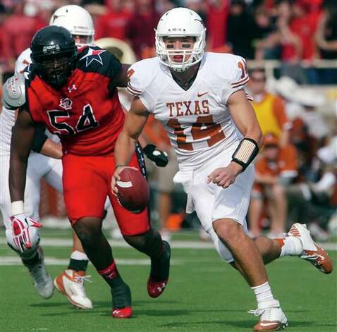Texas quarterback David Ash (14) scrambles away from Texas Tech's defensive end Dartwan Bush (54) during their NCAA college football game, Saturday, Nov. 3, 2012, in Lubbock, Texas. Texas won 31-22. (AP Photo/The Odessa American, Albert Cesare) Photo: Albert Cesare, AP / The Odessa American