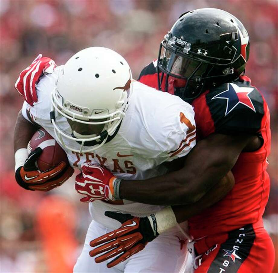 Texas Tech's Eugene Neboh, right, tackles Texas wide receiver Mike Davis (1) during their NCAA college football game, Saturday, Nov. 3, 2012, in Lubbock, Texas. Texas won 31-22. (AP Photo/The Odessa American, Albert Cesare) Photo: Albert Cesare, AP / The Odessa American