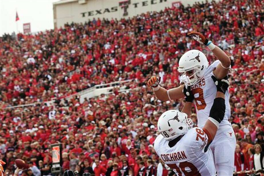Texas offensive tackle Josh Cochran (78) lifts Jaxon Shipley (8) in the air after Shipley scored a touchdown against Texas Tech during the first quarter of their NCAA college football game, Saturday, Nov. 3, 2012, in Lubbock, Texas. Texas won 31-22. (AP Photo/The Odessa American, Albert Cesare) Photo: Albert Cesare, AP / The Odessa American