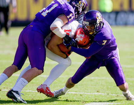 East Carolina's Damon Magazu (11) and Rio Johnson (7) tackle Houston's Shane Ros (19) during their NCAA college football game, Saturday, Nov. 3, 2012, in Greenville, N.C. East Carolina won 48-28. (AP Photo/The Daily Reflector, Scott Davis) Photo: Scott Davis, Associated Press / The Daily Reflector