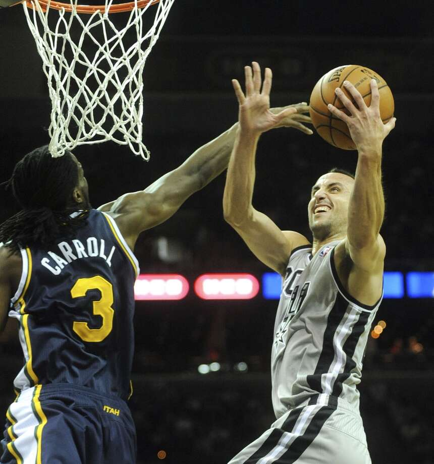 Manu Ginobili of the San Antonio Spurs scores as DeMarre Carroll of the Utah Jazz attempts the block during second-quarter NBA action at the AT&T Center on Saturday, Nov. 3, 2012. (San Antonio Express-News)