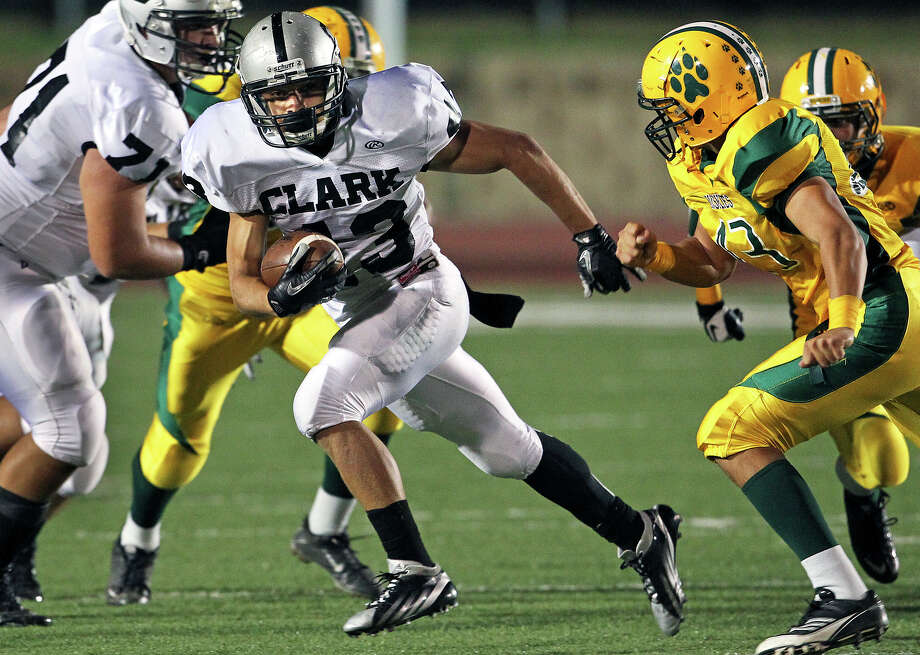 Cougar tailback Branden Valle harvests more yards on the right as Holmes plays Clark at Gustafson Stadium on November 3, 2012. Photo: Tom Reel, Express-News / ©2012 San Antono Express-News