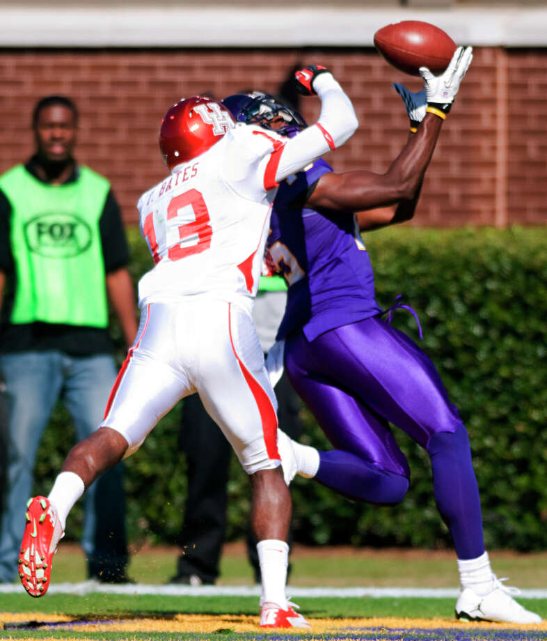 East Carolina's Reese Wiggins (15) catches a touchdown pass over Houston's Thomas Bates (13) during their NCAA college football game, Saturday, Nov. 3, 2012, in Greenville, N.C. East Carolina won 48-28. (AP Photo/The Daily Reflector, Scott Davis) Photo: Scott Davis, Associated Press / The Daily Reflector