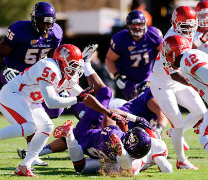 East Carolina's Vintavious Cooper (21) is brought down by Houston's Kent Brooks (24) during their NCAA college football game, Saturday, Nov. 3, 2012, in Greenville, N.C. East Carolina won 48-28. (AP Photo/The Daily Reflector, Scott Davis) Photo: Scott Davis, Associated Press / The Daily Reflector