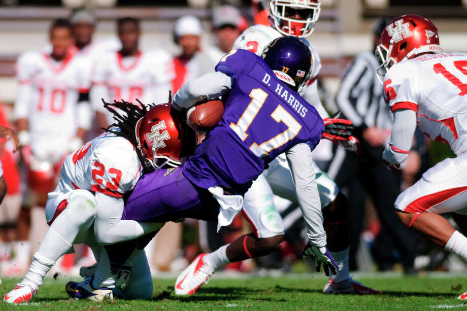 East Carolina's Derrick Harris (17) is brought down by Houston's Trevon Stewart (23) during their NCAA college football game, Saturday, Nov. 3, 2012, in Greenville, N.C. East Carolina won 48-28. (AP Photo/The Daily Reflector, Scott Davis) Photo: Scott Davis, Associated Press / The Daily Reflector