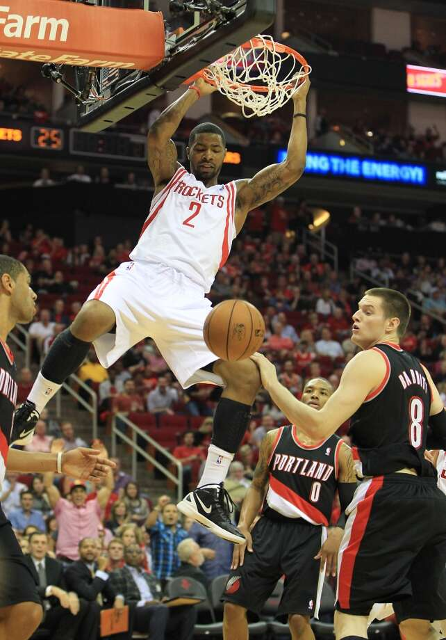 Houston's Marcus Morris (2) hangs from the basket after scoring against Portland's Luke Babbitt (8) during the first half of the home opener NBA game at Toyota Center, Saturday, Nov. 3, 2012, in Houston. (Karen Warren / Houston Chronicle)