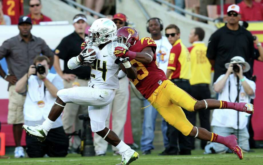 Oregon's Kenjon Barner takes Southern Cal's Jawanza Starling along for ride while scoring on a 27-yard run that was one of many highlights by Barner on his 321-yard night. Photo: Stephen Dunn, Staff / 2012 Getty Images