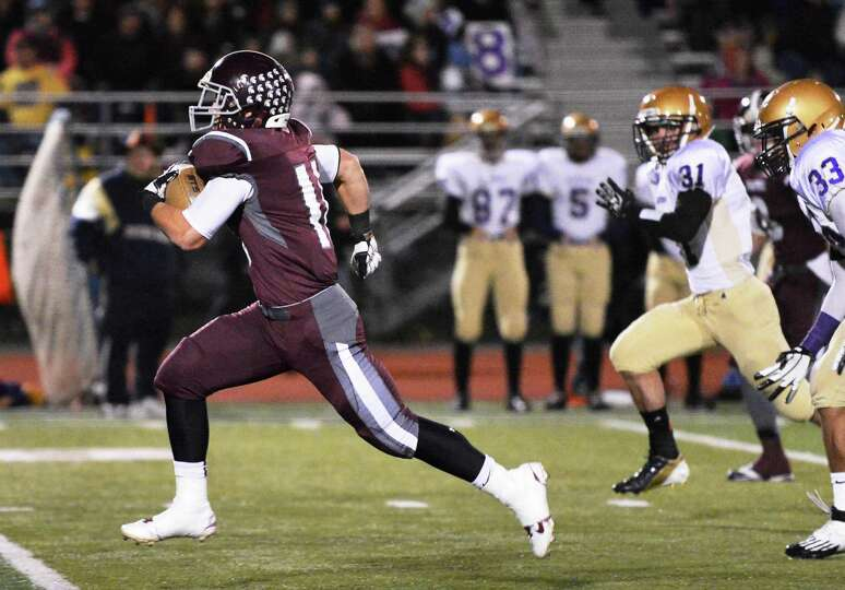 Burnt Hills' #11 Dan Maynard,left, breaks away from Amsterdam defenders to score a TD in the Class A