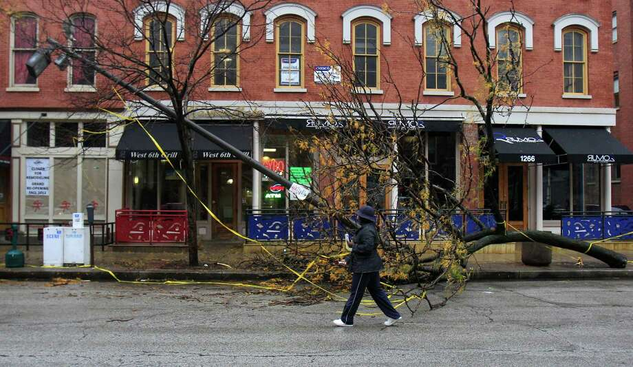A woman walks around a fallen tree and light pole blocking the sidewalk in the aftermath of superstorm Sandy, Wednesday, Oct. 31, 2012, in downtown Cleveland. (AP Photo/Tony Dejak) Photo: Tony Dejak