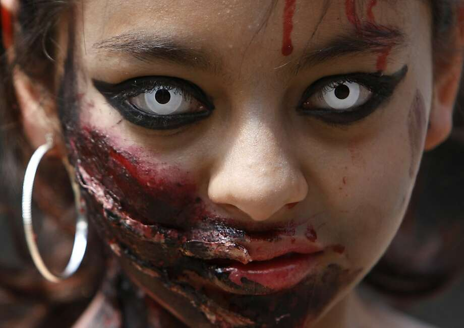 A woman in zombie make-up looks at the camera as she takes part in the Zombie Walk in Mexico City, Saturday, Nov. 3, 2012. According to the organization Zombie Walk Mexico, they are trying to set a new Guinness World Record for the biggest Zombie Walk. (AP Photo/Marco Ugarte) Photo: Marco Ugarte, Associated Press