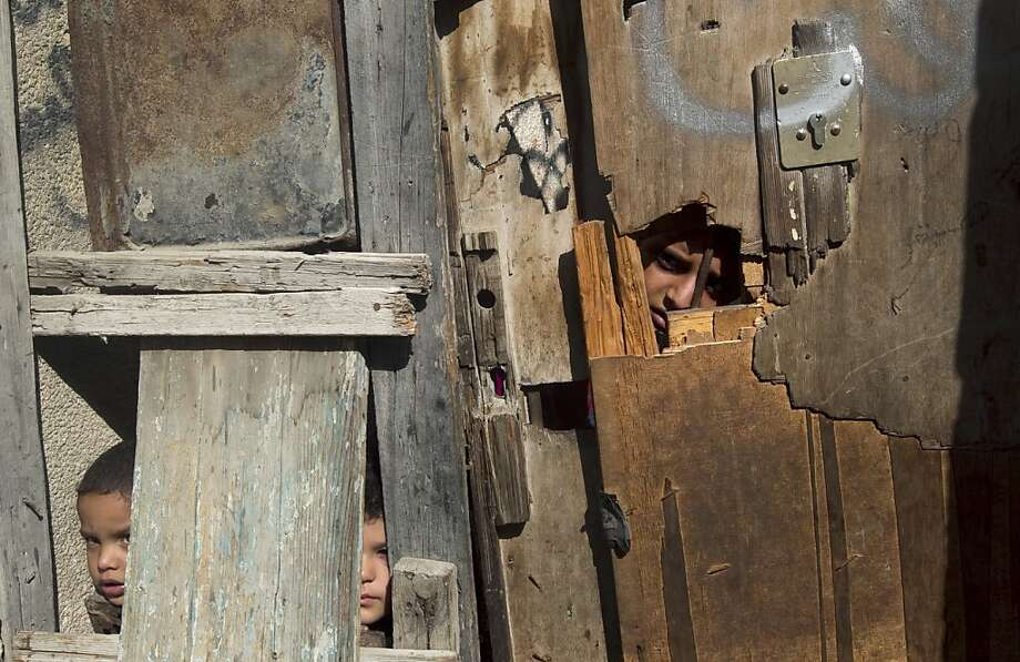 "The kids whom nobody wants: Palestinian children peer through a ramshackle wooden door at the Shati Palestinian refugee camp in Gaza City. Palestinians demand that Israel recognize the ""right of return"" of refugees to Israel. Israel rejects the demand, saying they should be accommodated within a Palestinian state. Photo: Mahmud Hams, AFP/Getty Images"