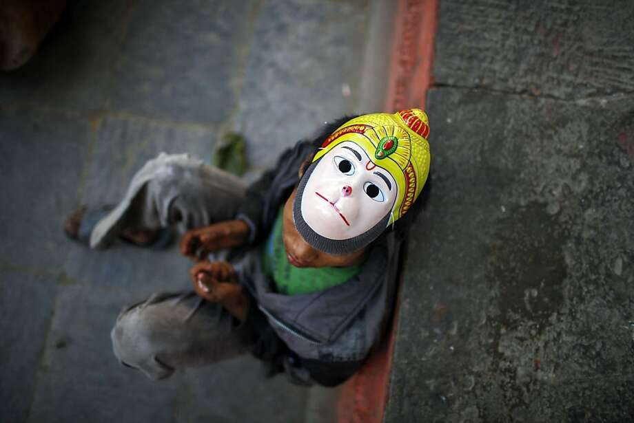 A Nepalese street child, wearing a mask of Hindu monkey God Hanuman, rests on a street in Katmandu, Nepal, Friday, Nov. 2, 2012. Photo: Niranjan Shrestha, Associated Press
