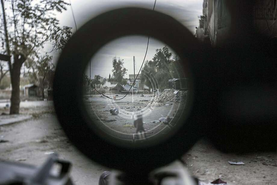 In this Friday, Nov. 02, 2012 photo, a sniper line-of-fire is seen through the scope of a rebel fighter's gun in the Karm al-Jebel neighborhood in Aleppo, Syria. U.N. officials and human rights groups believe President Bashar Assad's regime is responsible for the bulk of suspected war crimes in Syria's 19-month-old conflict, which began as a largely peaceful uprising but has transformed into a brutal civil war. However a video that appears to show a unit of Syrian rebels kicking terrified, captured soldiers and then executing them with machine guns raised concerns Friday about rebel brutality at a time when the United States is making its strongest push yet to forge an opposition movement it can work with. Photo: Narciso Contreras, Associated Press