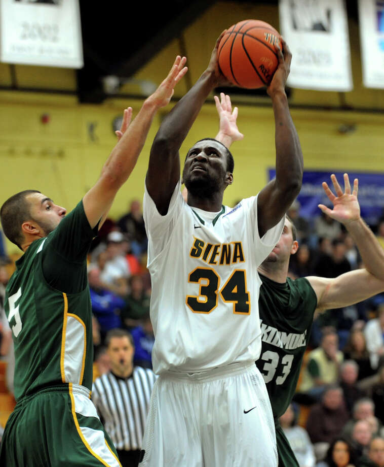 Siena's Imoh Silas (34), center, aims for the hoop as Skidmore's Aldin Medunjanin (5), left, and Connor Merrill (33) defend during their exhibition basketball game on Saturday, Nov. 3, 2012, at Siena College in Loudenville, N.Y. (Cindy Schultz / Times Union) Photo: Cindy Schultz / 00019935A