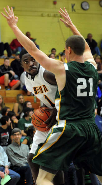 Siena's O.D. Anosike(1), left, looks to pass as Skidmore's Kevin Dahill (21) defends during their ex