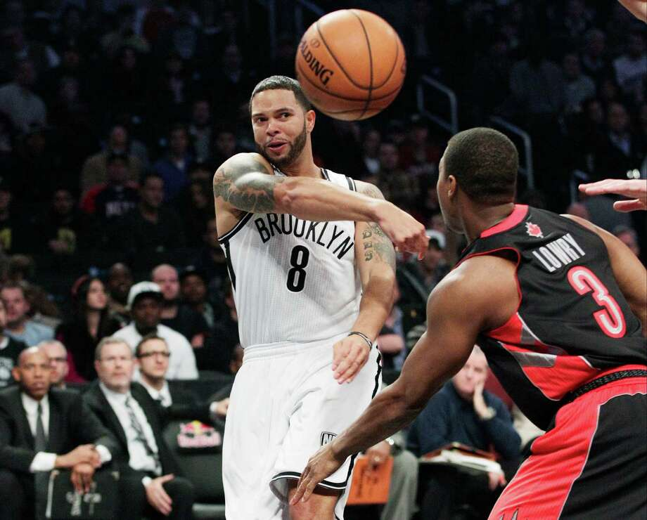Brooklyn Nets' Deron Williams (8) passes away from Toronto Raptors' Kyle Lowry (3) during the first half of an NBA basketball game, Saturday, Nov. 3, 2012, in New York. (AP Photo/Frank Franklin II) Photo: Frank Franklin II