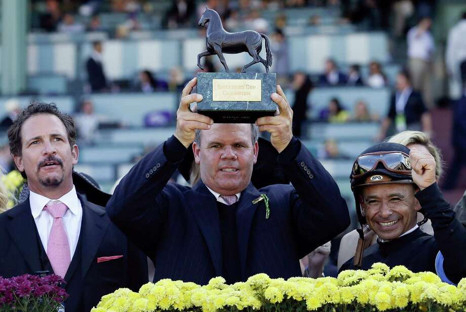 Trainer Mike Puype, center, holds up the trophy in the winner's circle as owner Jim Rome, left, and jockey Mike Smith, right, look on after Mizdirection won the Breeders' Cup Turf Sprint horse race, Saturday, Nov. 3, 2012, at Santa Anita Park in Arcadia, Calif. (AP Photo/Gregory Bull) Photo: Gregory Bull