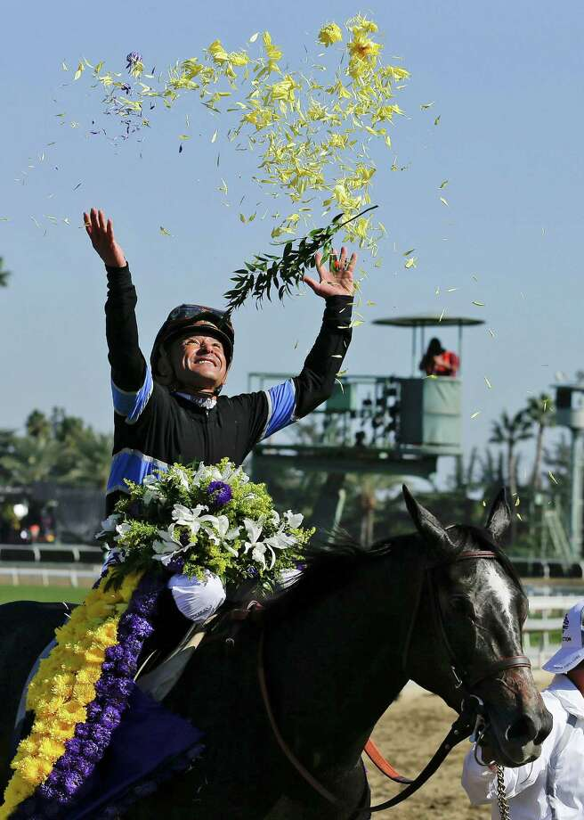 Jockey Mike Smith tosses flower petals in the air after riding Mizdirection to win the Breeders' Cup Turf Sprint horse race with Mizdirection, Saturday, Nov. 3, 2012, at Santa Anita Park in Arcadia, Calif. (AP Photo/Gregory Bull) Photo: Gregory Bull