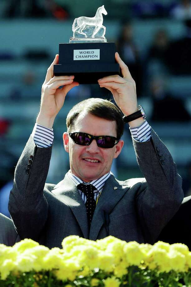 Aidan O'Brien, trainer for George Vancouver, holds up the trophy for the Breeders' Cup Juvenile Turf horse race, Saturday, Nov. 3, 2012, at Santa Anita Park in Arcadia, Calif. (AP Photo/Gregory Bull) Photo: Gregory Bull