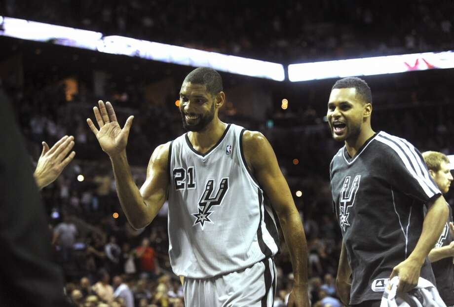 Tim Duncan, left, and Patty Mills of the San Antonio Spurs smile as they leave the court following the team's 110-100 victory over the Utah Jazz in NBA action at the AT&T Center on Saturday, Nov. 3, 2012. (San Antonio Express-News)