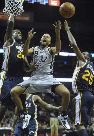 San Antonio's Tony Parker (9) is fouled by Paul Millsap (24) of the Utah Jazz as Al Jefferson, right, defends during NBA action at the AT&T Center on Saturday, Nov. 3, 2012. (San Antonio Express-News)