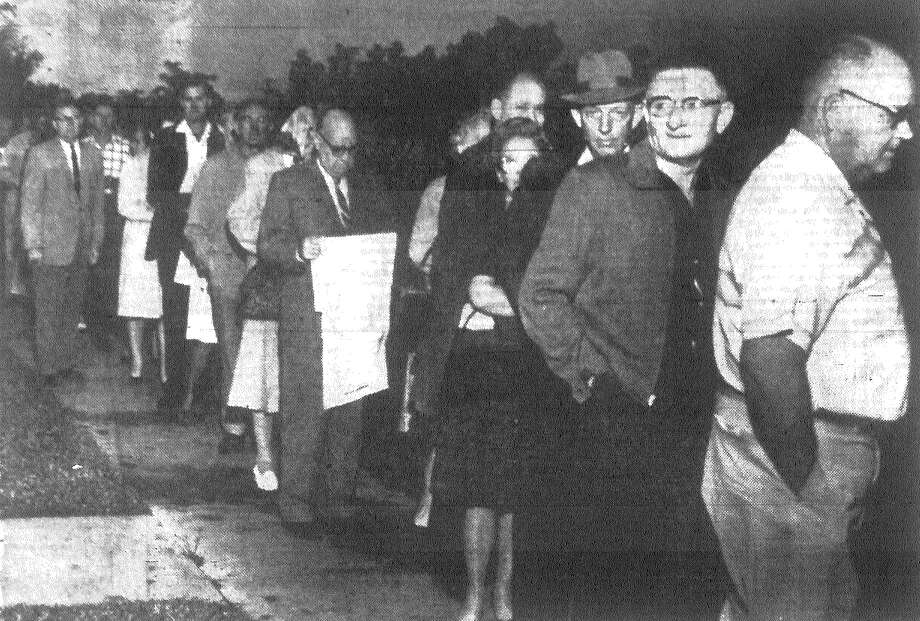 A line of Bexar County voters awaited election judges at many precincts. Here one voter studies the long ballot as he waits to vote. Election judges reported voters were moving through the voting machines rapidly despite forecasts that voting would be slow. Published in the San Antonio News Nov. 6, 1962. Photo: File Photo