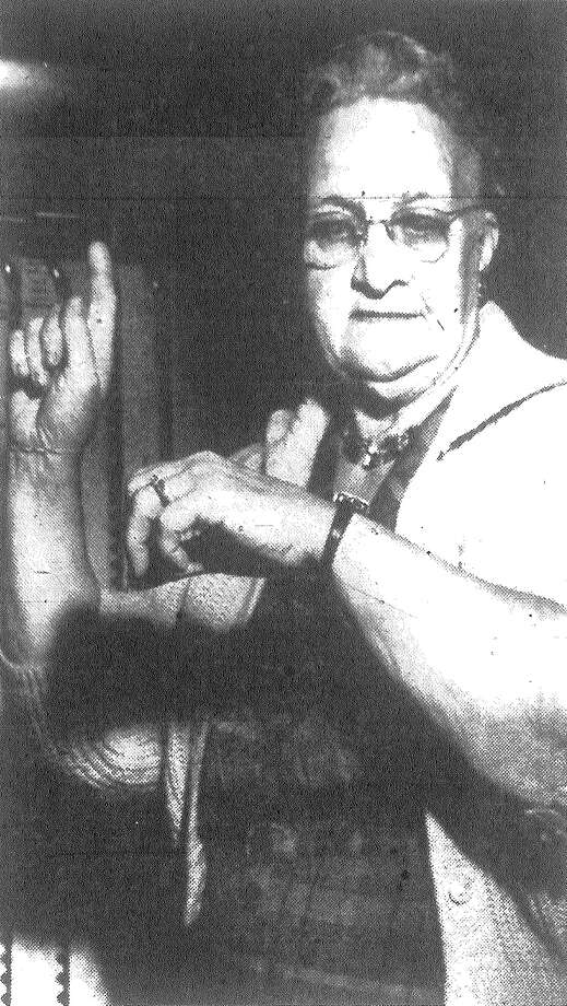 Mrs. L.J. Tolle, election judge at Precinct 67, Fire Station No. 20, starts countdown to open elections at that precinct. Some precincts didn't get election machines operating on time but most got under way promptly at 7 a.m. Published in the San Antonio News Nov. 6, 1962. Photo: File Photo