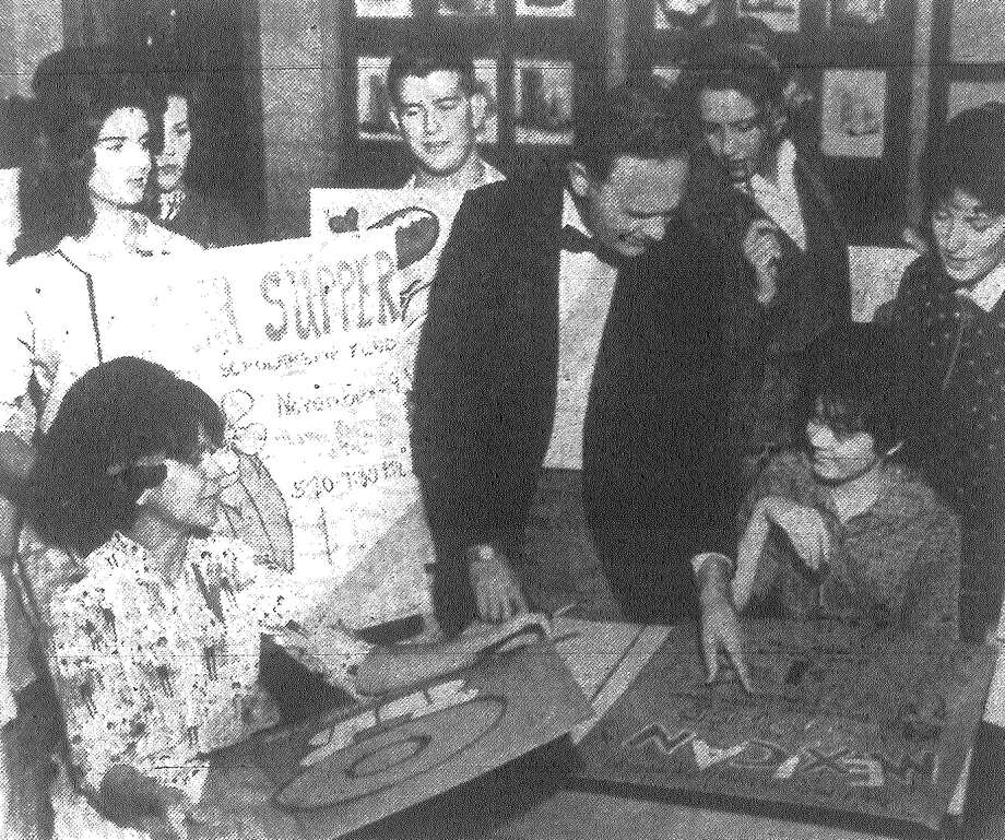 Students in Alamo Heights High School art classes huddle around instructor John Squire Adams as he goes over a poster for the upcoming Mexican supper with Sally Turan, seated at right. Money will go for Parent-Teacher Organization scholarships. Published in the San Antonio Express Nov. 4, 1962. Photo: File Photo