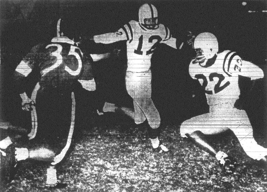 Larry Peel (12) takes off on a five-yard jaunt past onrushing Harlandale defense as teammate Madison Preacher (22) of Highlands cuts in to provide some blocking for Peel in first-quarter action. Published in the San Antonio Light Nov. 3, 1962. Photo: File Photo