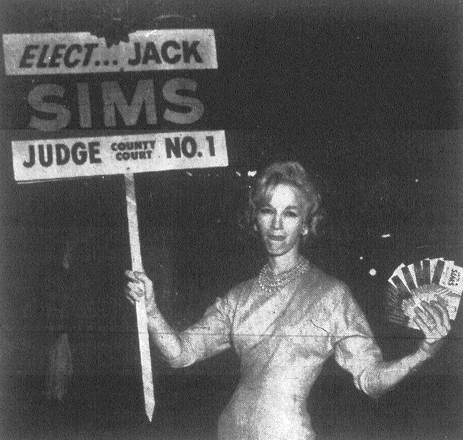 Mrs. Ann Harper waves a Jack Sims sign and literature during her campaign on Houston Street. She and her sister are seeking to whip up support to defeat County Court-at-Law Judge McCollum Burnett. Mrs. Harper claims she hasn't been getting a fair deal in Burnett's court. Mrs. Harper and her sister have set up their headquarters in front of the Manhattan Cafe. Published in the San Antonio News Nov. 2, 1962. Photo: File Photo