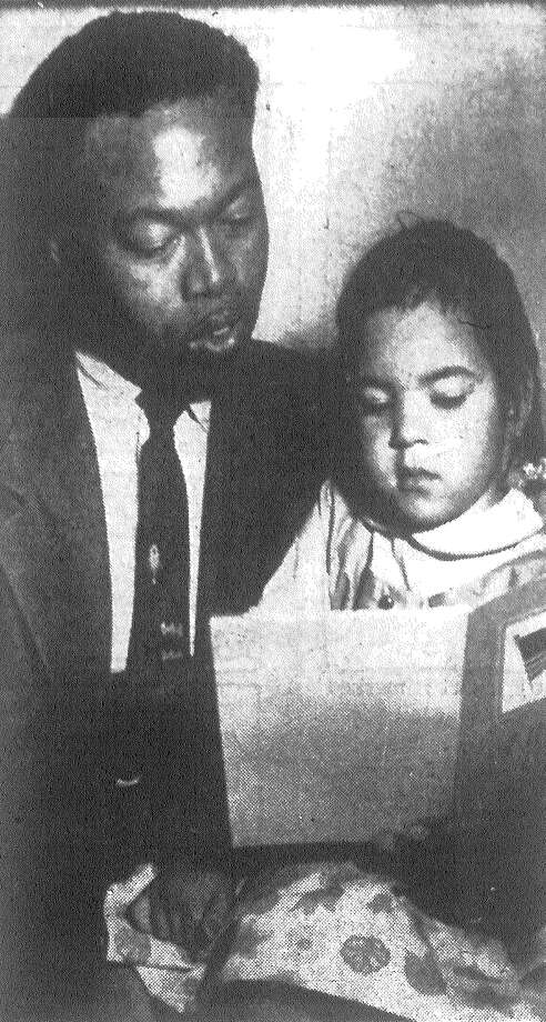 Sgt. Harvey A. Collins reads to the three-year-old girl he adopted in Germany and brought to the U.S. Little Augusta Antoninette Collins became an American citizen in naturalization ceremonies here.  Published in the San Antonio Express Nov. 14, 1962. Photo: File Photo