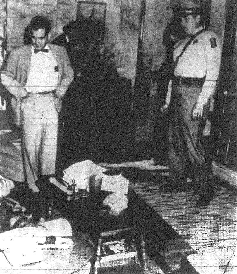 Dr. Robert Hausman, county medical examiner, and Castle Hills Chief of Police Richard Scheppler, right, view the body of Mrs. Sabina Dibble as it lies on a couch in her home. A shotgun believed to be the weapon used in the shooting is beside the table, foreground. Her husband, Jack Dibble, is being held for the slaying. Published in the San Antonio Light Nov. 12, 1962. Photo: File Photo