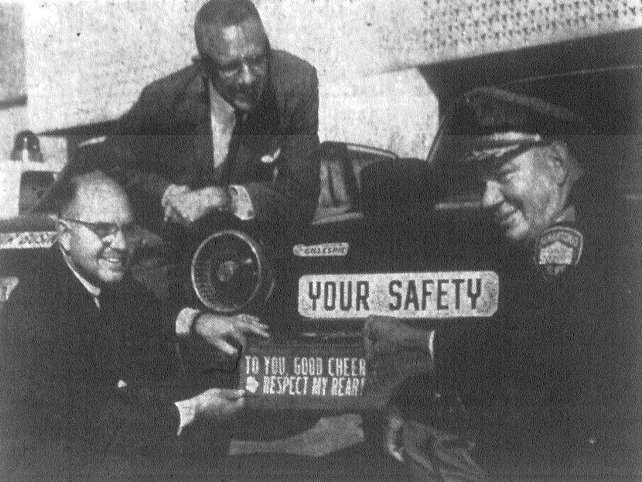 Roy Akers, kneeling at left, and Inspector John Fitch of the San Antonio Police Department, put a bumper sticker on a car to launch a campaign to keep down the number of Yule season accidents. Akers is president of the Greater San Antonio Safety Council. Watching the proceedings with approval is Police Chief George Bichsel. Published in the San Antonio News Nov. 15, 1962. Photo: File Photo