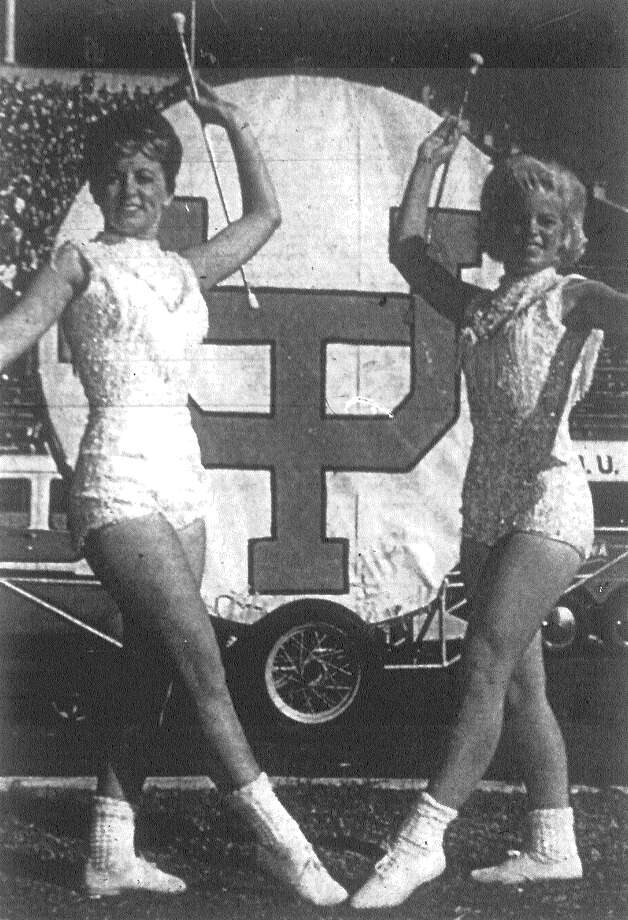 "Featured performers when the University of Texas band gives its halftime show in Austin Thanksgiving — and before a national CBS television audience — will be Irene and Carol Reeb, sisters from Calallen. They are featured twirlers with the band. Irene is on the left, Carol on the right. ""Big Bertha,"" the band's famous ""largest drum in the world,"" is in the background. Published in the San Antonio Express Nov. 15, 1962. Photo: File Photo"
