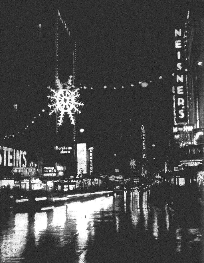 The city's rain-washed streets this week reflect the twinkling lights of the downtown area Christmas decorations, resulting in the beautiful night-time scene above, looking west on Houston Street. Published in the San Antonio Express Nov. 29, 1962. Photo: File Photo