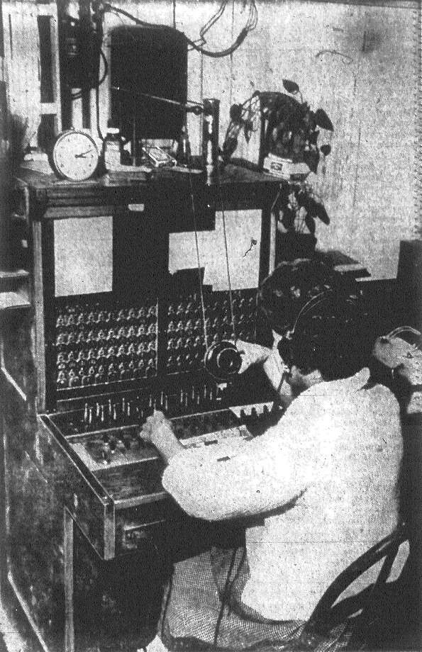 Nora Cortez, D'Hanis' lone switchboard operator, handles the town's calls from a small room over the town's general store. D'Hanis will soon be replacing its crank telephones with dial telephones. Published in the San Antonio Light Nov. 24, 1962. Photo: File Photo