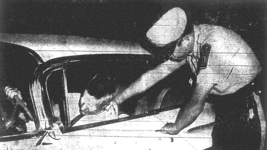 A policeman grips the collar of an alleged intoxicated driver still behind the wheel. Published in the San Antonio Light Nov. 18, 1962. Photo: File Photo