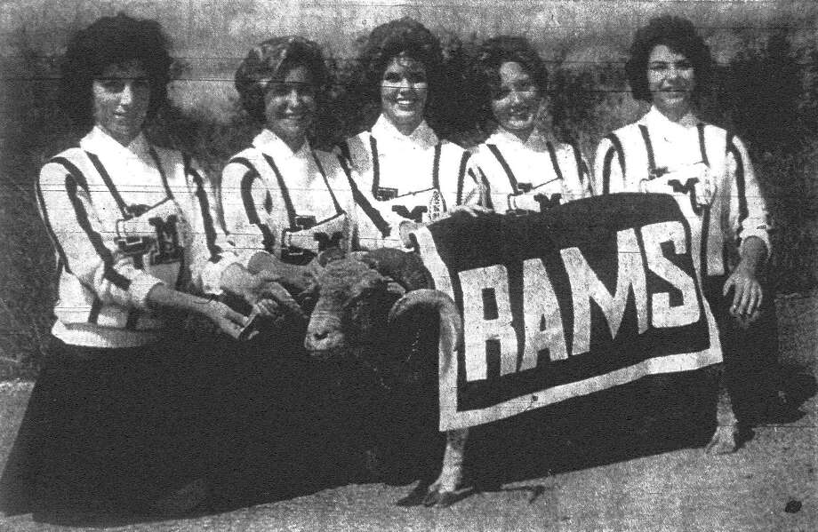 Colleges, of course, have mascots to inspire their athletic teams but for a high school they're not so common. At John Marshall High, it's a ram that bolsters team drive. Lending a pampering hand to the wooly creature are, from left to right, Nancy Leyda, Suzie Dolch, Bonnie Stuebing, Sue Bacon and Jan Dolch. The students are studying agriculture care for the animal. Published in the San Antonio Light Nov. 20, 1962. Photo: File Photo