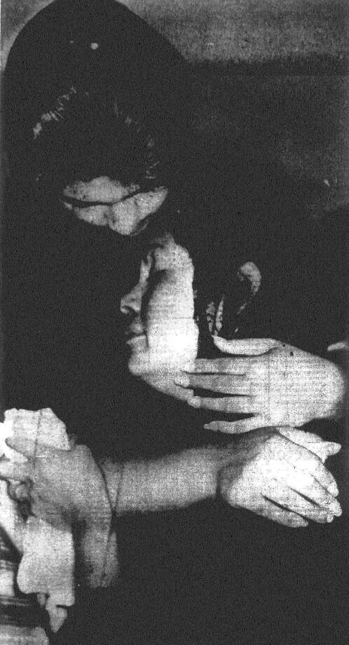 Mrs. Emilia Aguilar stems her tears as her eldest daughter enfolds her in a comforting embrace as Mrs. Aguilar awaits an examining trial on charges she fatally shot her husband. The examining trial was later waived and she was released on a $5,000 bond Wednesday. Published in the San Antonio Express Nov. 29, 1962. Photo: File Photo