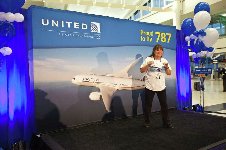 Jennifer Curry stands on a stage holding a ticket to fly as United Airlines - the North American launch customer for the Boeing 787 -flew its first scheduled commercial 787 flight from Houston to Chicago, with more than 200 customers on board Nov. 4, 2012 in Houston at Bush International Airport. Curry is a United employee based at Dulles International Airport in Washington, DC. Photo: Eric Kayne / © 2012 Eric Kayne