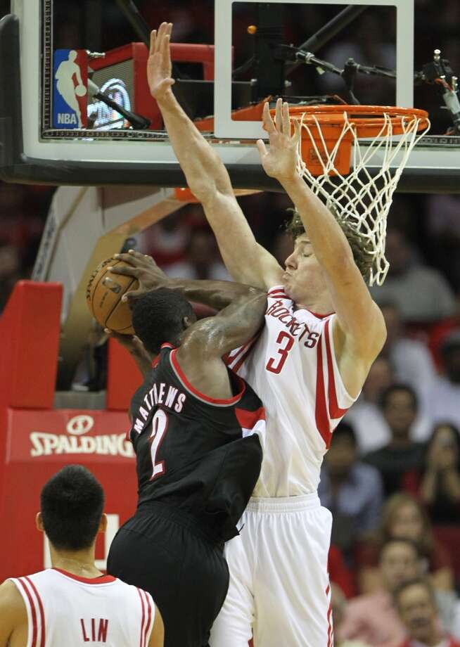 Wesley Matthews of the Trail Blazers tries a drive over Rockets center Omer Asik. (Karen Warren / Houston Chronicle)